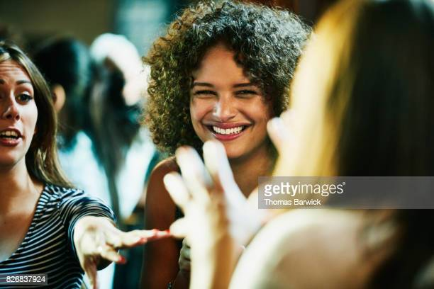laughing woman hanging out with friends in bar - partage photos et images de collection