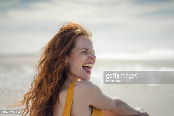 laughing woman having fun on the beach - zomer stockfoto's en -beelden