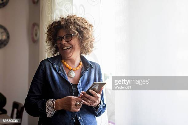 laughing woman holding phablet by the window - 50 54 years stock pictures, royalty-free photos & images