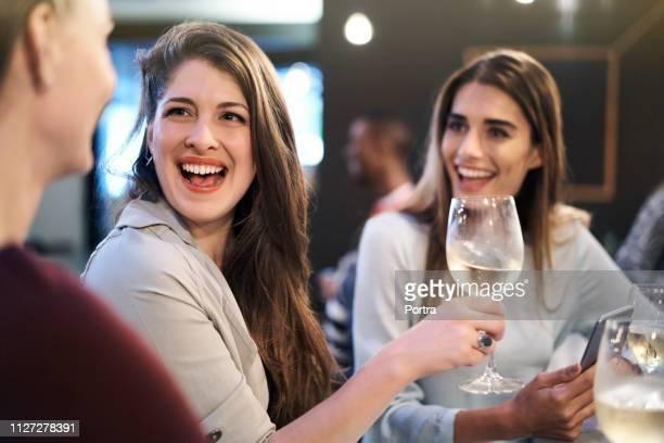 femme riante retenant le verre de vin par des amis dans le bar - seulement des jeunes femmes photos et images de collection