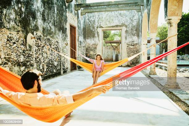 Laughing woman in discussion with boyfriend while relaxing in hammocks at luxury resort