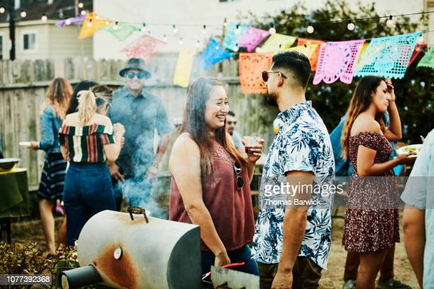 laughing woman in discussion with friend during backyard barbecue on summer evening - mexican ethnicity stock pictures, royalty-free photos & images