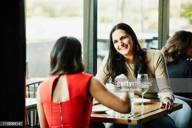Laughing woman in discussion with friend while sharing drinks in restaurant