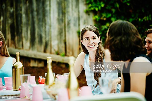 Laughing woman in discussion with friends at party