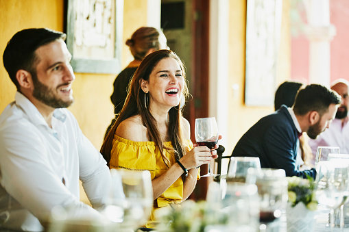Laughing woman in discussion with friends during wedding reception dinner - gettyimageskorea