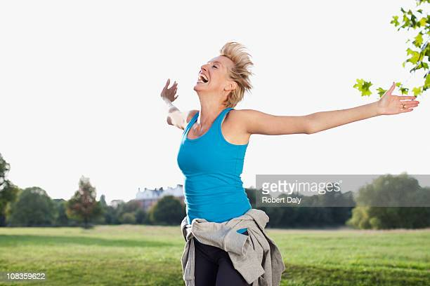 Laughing woman in field with arms outstretched
