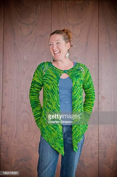 laughing woman in green sweater, walnut paneling
