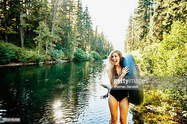 Laughing woman in swimsuit holding inner tube
