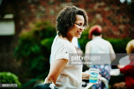 Laughing Woman In The Rain During Backyard Party Stock Photo