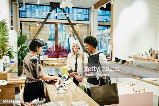 Laughing woman looking at shirt while checking out after shopping in boutique with friend