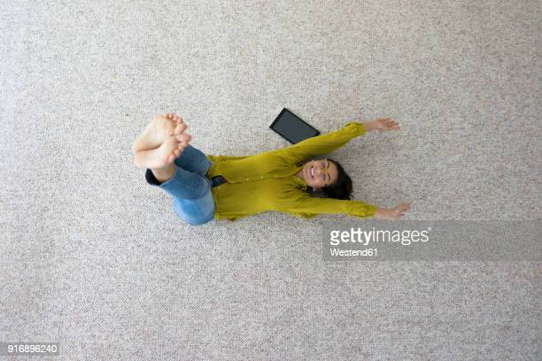Laughing woman lying on carpet doing stretching exercises, top view