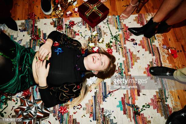 laughing woman lying on floor covered in bows and confetti during holiday party with friends - despreocupado fotografías e imágenes de stock