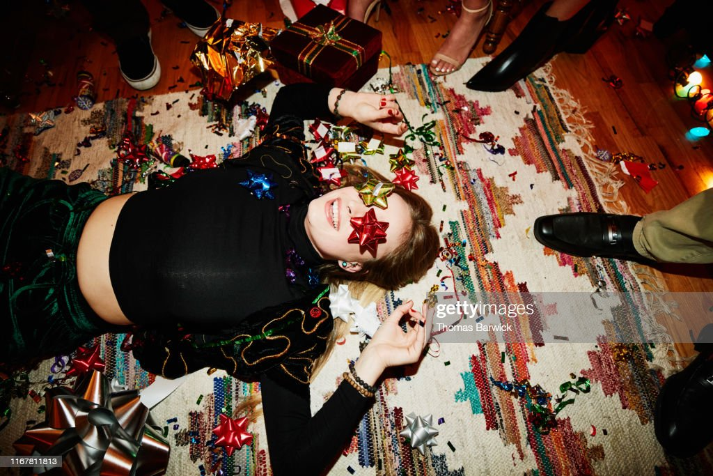 Laughing woman lying on floor with bows over eyes during holiday party with friends : Stock Photo