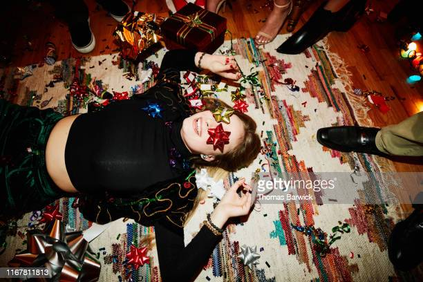 laughing woman lying on floor with bows over eyes during holiday party with friends - christmas fotografías e imágenes de stock