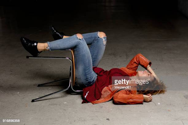 Laughing woman lying on the floor with chair