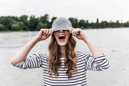 Laughing woman playing with wooly hat at a river - gettyimageskorea