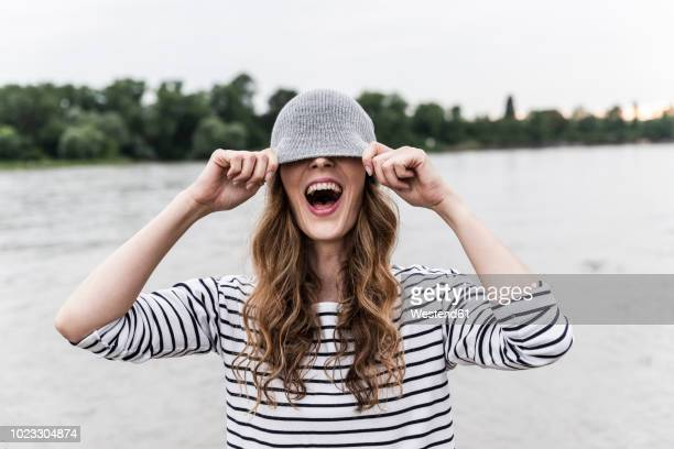 laughing woman playing with wooly hat at a river - fashion stock-fotos und bilder