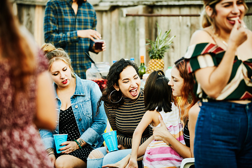 Laughing woman playing with young girl during backyard barbecue on summer evening - gettyimageskorea