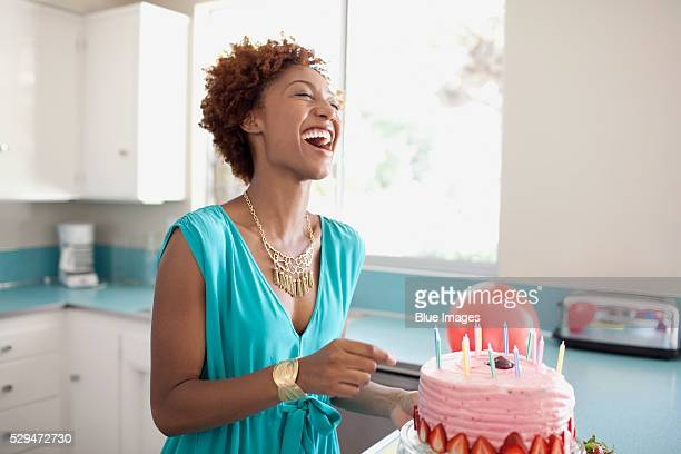 laughing woman preparing birthday cake - woman birthday stock pictures, royalty-free photos & images