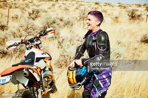 Laughing woman preparing to put on helmet before dirt bike ride in desert with friends