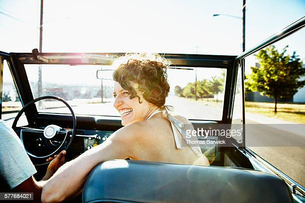 Laughing woman riding in convertible