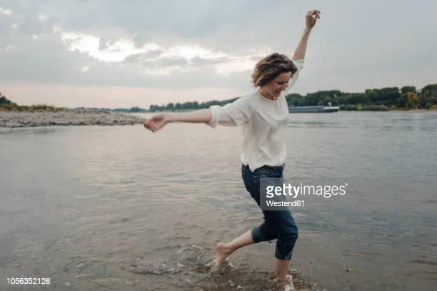 laughing woman running at the riverside - one mature woman only stock pictures, royalty-free photos & images