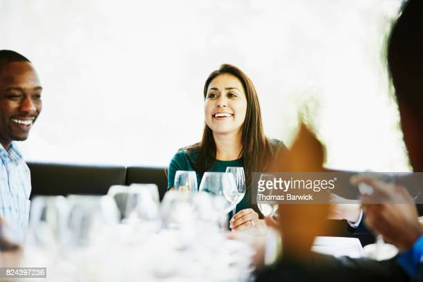 Laughing woman sharing a meal with friends in restaurant