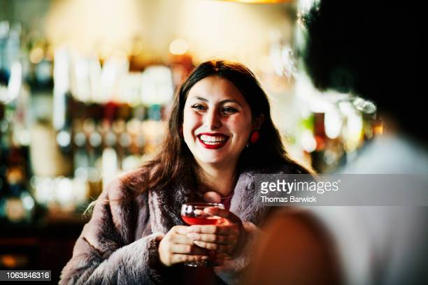 Laughing woman sharing drinks with friends in bar
