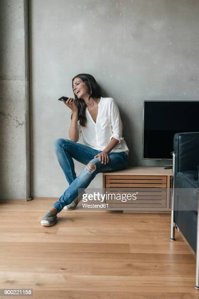 Laughing woman sitting down using cell phone