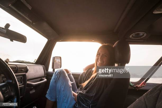 laughing woman sitting in car at sunset - landvoertuig stockfoto's en -beelden