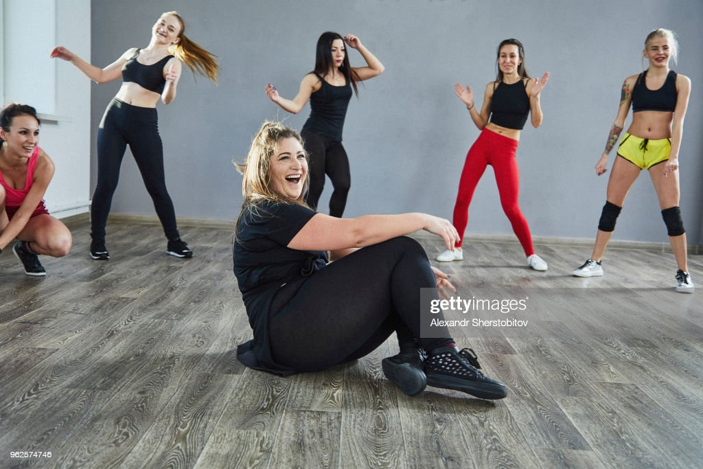 Laughing woman sitting on floor while dancing with friends at studio : Stock Photo