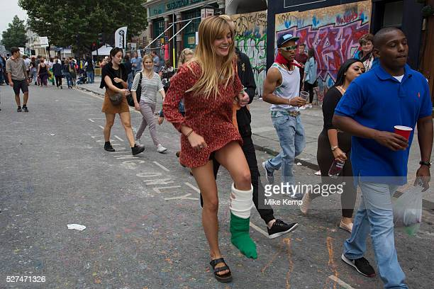 Laughing woman stil lenjoys the day despite her broken leg which is in a cast Notting Hill Carnival in West London A celebration of West Indian /...