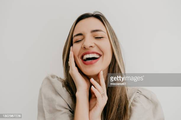 laughing woman touching cheek with eyes closed against white background - cheek stock pictures, royalty-free photos & images