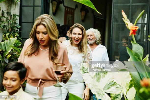 Laughing woman walking into backyard with family during dinner party