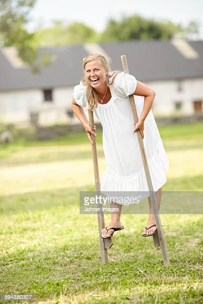 Laughing woman walking on stilts