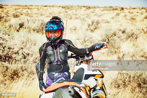 Laughing woman warming up dirt bike before desert ride