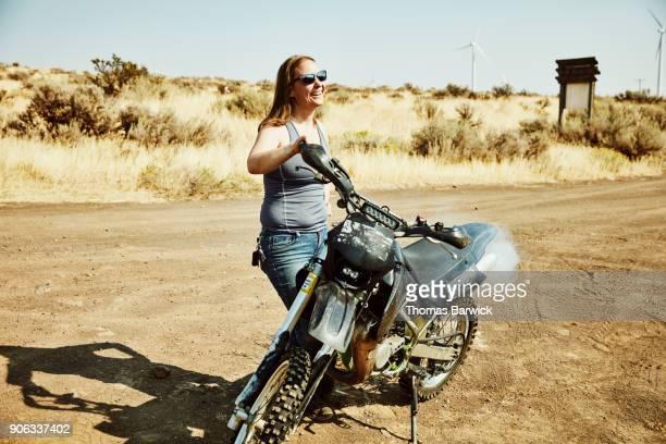 Laughing woman warming up dirt bike before ride in desert