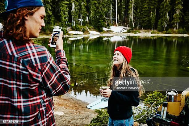 Laughing woman watching boyfriend use smartphone