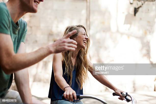 Laughing woman with bicycles beside her partner