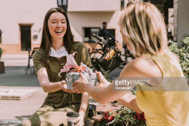 laughing woman with taken off face mask handing over gift to friend - giving stock pictures, royalty-free photos & images