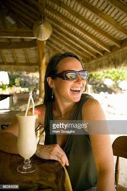 Laughing woman with tropical drink at bar