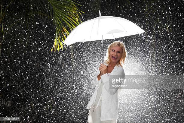 ridere donna con ombrello sotto la pioggia. - pioggia forte foto e immagini stock
