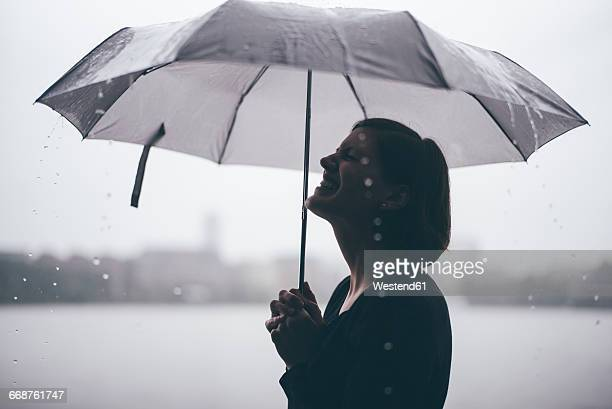 Laughing woman with umbrella on a rainy day