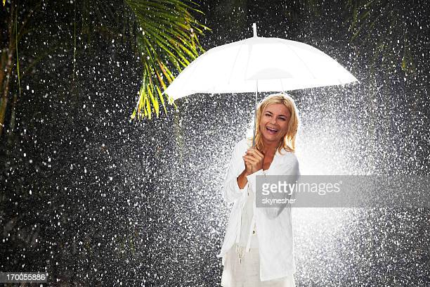 Laughing woman with umbrella on the rain.