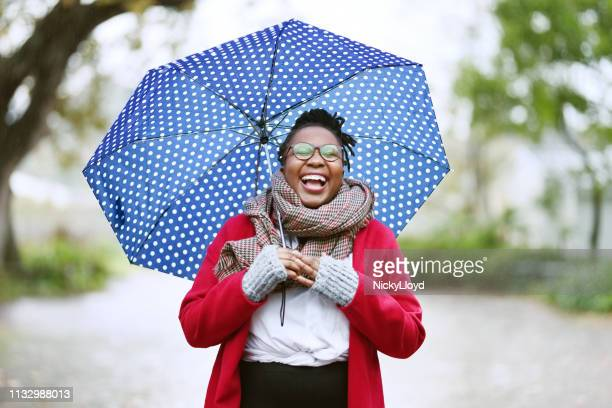 laughing woman with umbrella - umbrella stock pictures, royalty-free photos & images