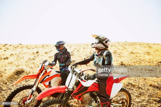 Laughing women in discussion while resting during dirt bike ride in desert