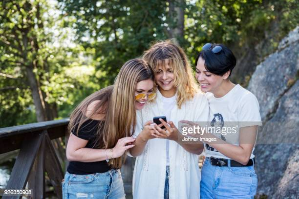 Laughing women looking at cell phone