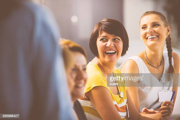 laughing women on seminar - werkplaats stockfoto's en -beelden