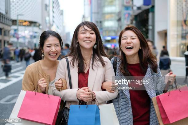Laughing women on street of shopping area