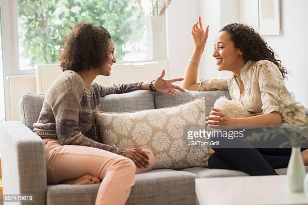 Laughing women talking on sofa
